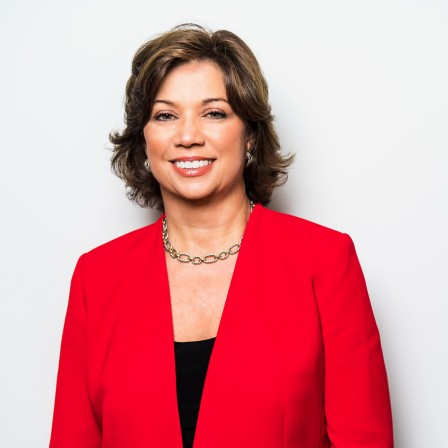 Deb Shaw in red jacket standing in front of white background smiling at camera